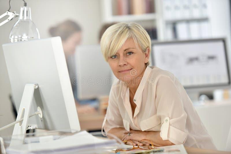 Portraot uśmiechnięty starszy bizneswoman przy biurem obraz royalty free