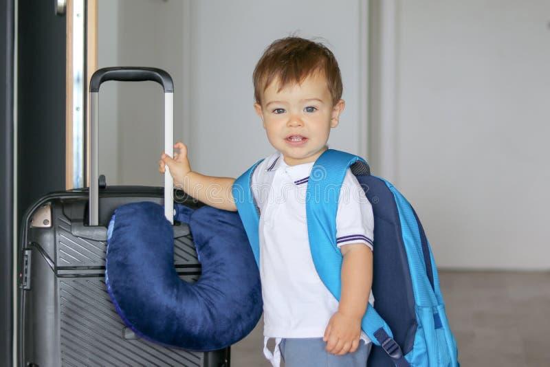 Portrat del primo piano di piccolo neonato sorridente sveglio con il grandi zaino e valigia con il soggiorno di viaggio del cusci fotografie stock libere da diritti