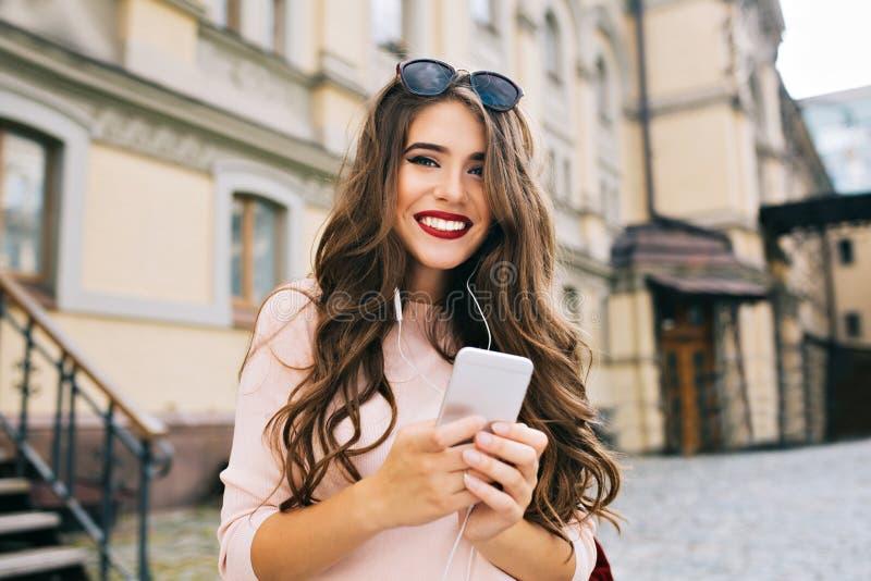 Portraut του χαριτωμένου κοριτσιού με τη μακριά σγουρή τρίχα και του τηλεφώνου στα χέρια που χαμογελούν στη κάμερα στην πόλη στην στοκ φωτογραφίες με δικαίωμα ελεύθερης χρήσης