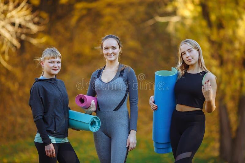 Portren av gruppen av unga kvinnor som förbereder sig för yogaövningar i höststaden, parkerar Vård- livsstilbegrepp arkivbilder