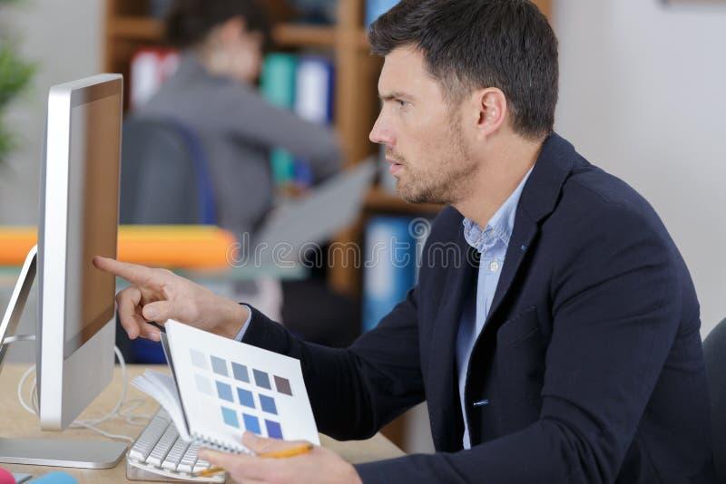 Portret?w projektant grafik komputerowych trzyma koloru swatch w biurze obrazy royalty free