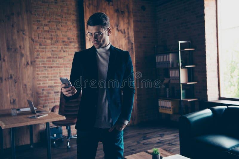 Portret ładnego przystojnego eleganckiego modnego inteligentnego faceta sms pisać na maszynie gadka wyszukuje app czekania partne zdjęcia royalty free