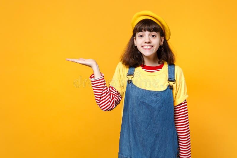Portret ładny dziewczyna nastolatek wskazuje rękę na boku odizolowywającą na kolor żółty ścianie w francuskich bereta i drelichu  obrazy royalty free