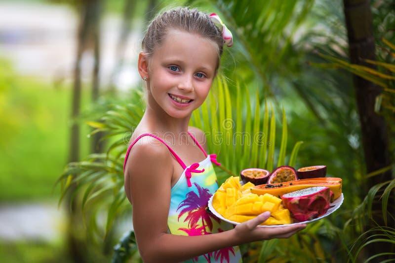 Portret śliczna dziewczyna w zwrotnikach Dziewczyna trzyma talerza z egzotycznymi owoc obrazy stock