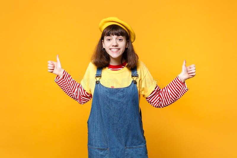 Portret śmieszny ładny dziewczyna nastolatek w francuskim berecie, drelichowi sundress pokazuje aprobaty odizolowywać na kolor żó zdjęcie stock