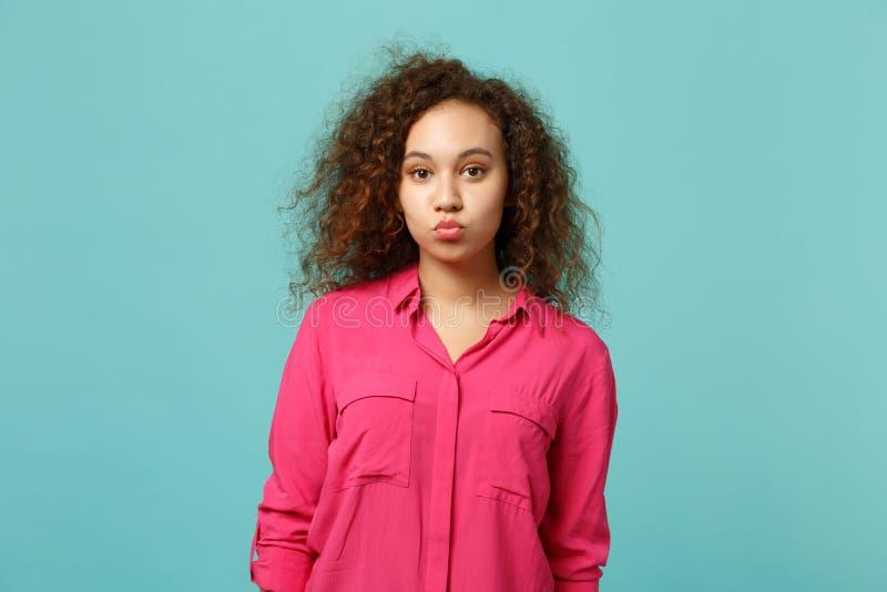 Portret ładna afrykańska dziewczyna dmucha dosłanie lotniczego buziaka odizolowywającego na błękitnej turkus ścianie w różowych p zdjęcia royalty free