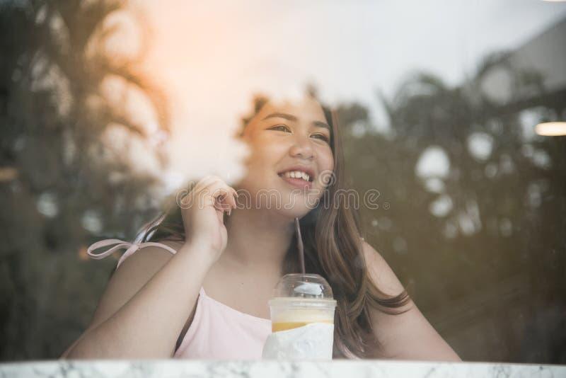 Portret Ładna Azjatycka gruba kobieta pije sok pomarańczowego i główkowanie zdjęcia stock
