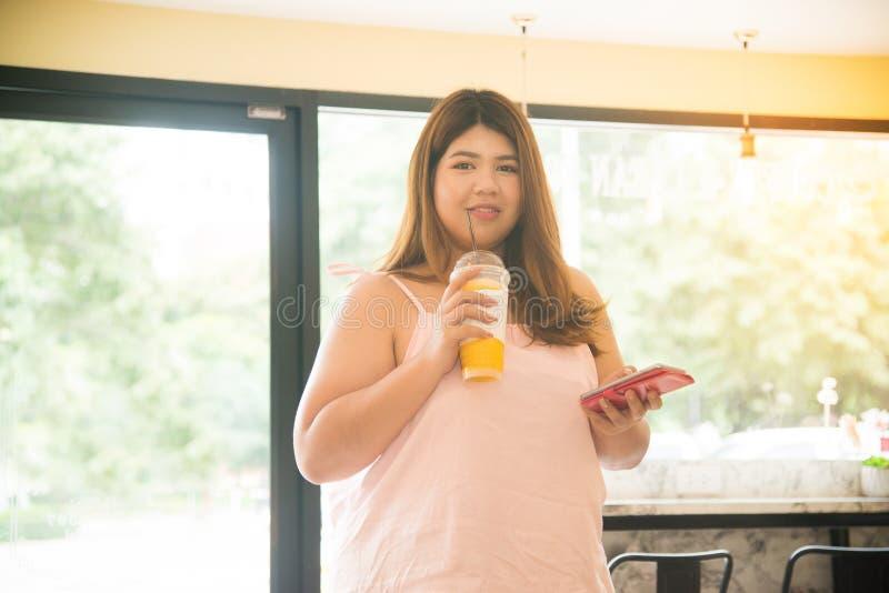 Portret Ładna Azjatycka gruba kobieta pije soku pomarańczowego i chwyta wiszącą ozdobę obrazy royalty free