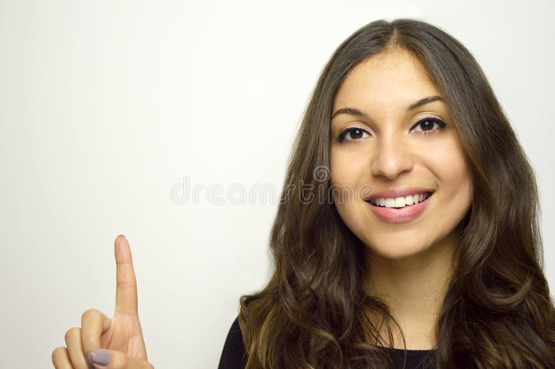 Portret ładna dziewczyna wskazuje palcowy daleko od odosobnionego na białym tle fotografia royalty free