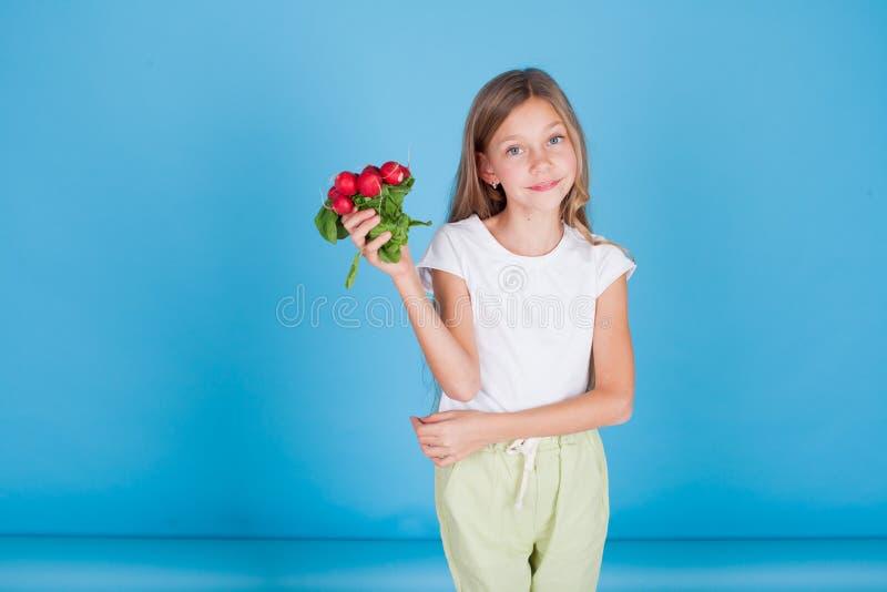 Portret ładna dziewczyna z świeżych warzyw czerwonymi rzodkwiami obraz stock