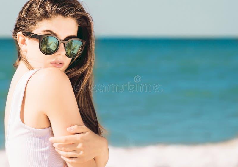 Portret ładna dziewczyna z długie włosy w modnych okularach przeciwsłonecznych z palmy odbiciem pozuje na plaży obrazy royalty free