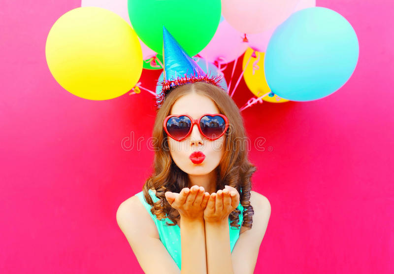 Portret ładna kobieta w urodzinowej nakrętce jest wysyła buziaka lotniczych chwyty lotniczy kolorowi balony na różowym tle zdjęcie royalty free