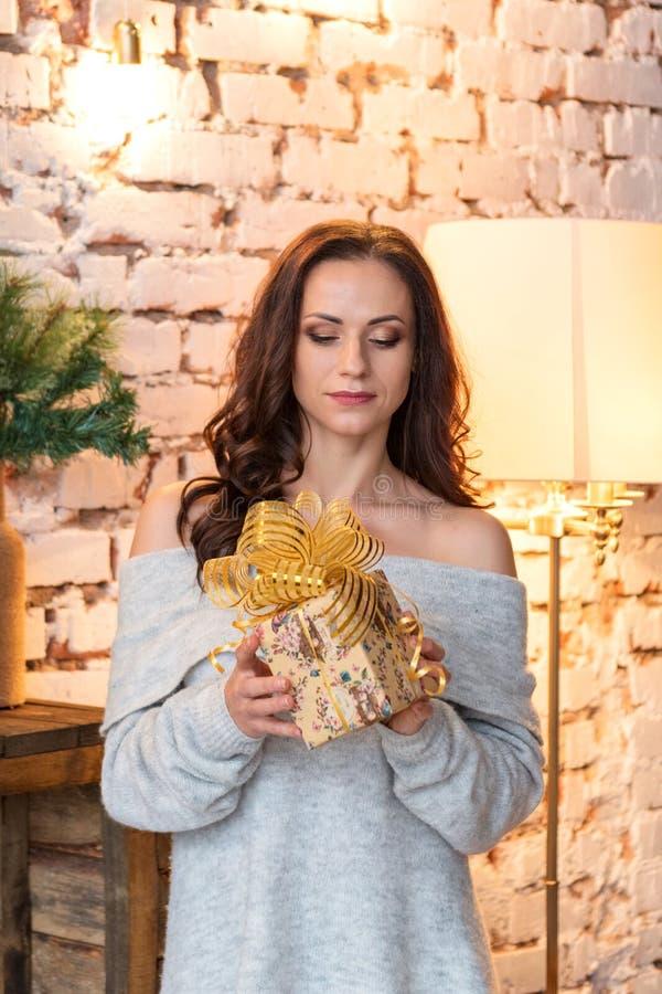Portret ładna młoda kobieta w wygodnym pulowerze egzamininuje prezent w świątecznym pakunku zdjęcia royalty free