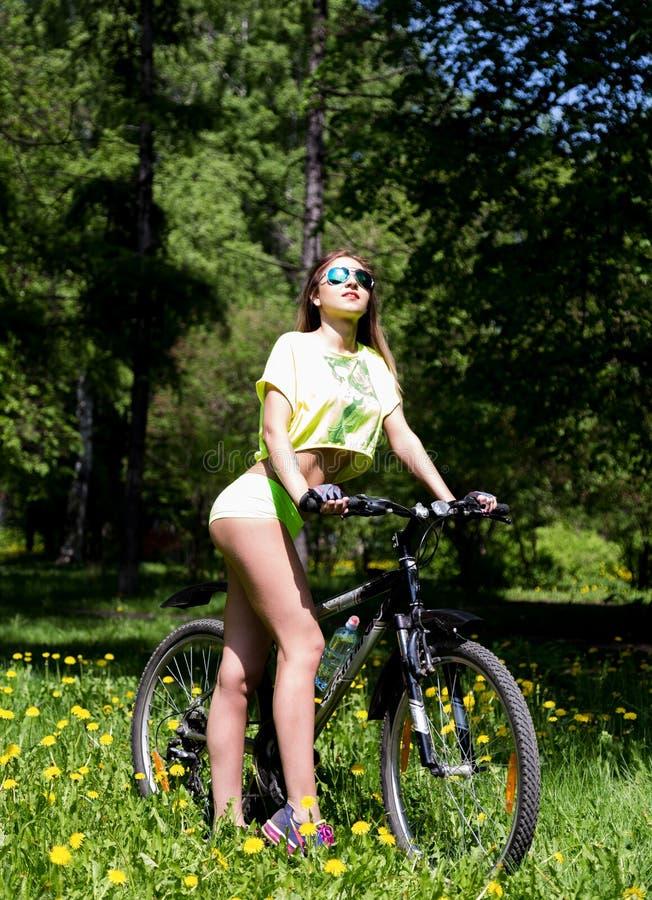 Portret ładna młoda kobieta z bicyklem w parku - plenerowym obraz stock