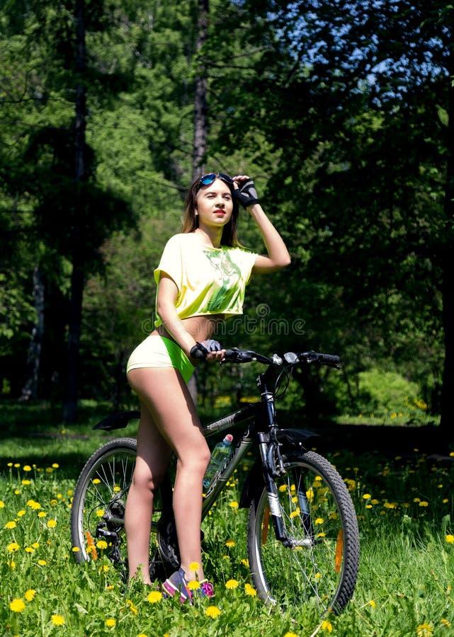Portret ładna młoda kobieta z bicyklem w parku - plenerowym zdjęcia royalty free