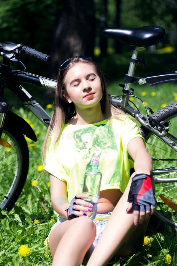 Portret ładna młoda kobieta z bicyklem w parku - plenerowym dziewczyny obsiadanie na napój wodzie od a i trawie zdjęcia royalty free