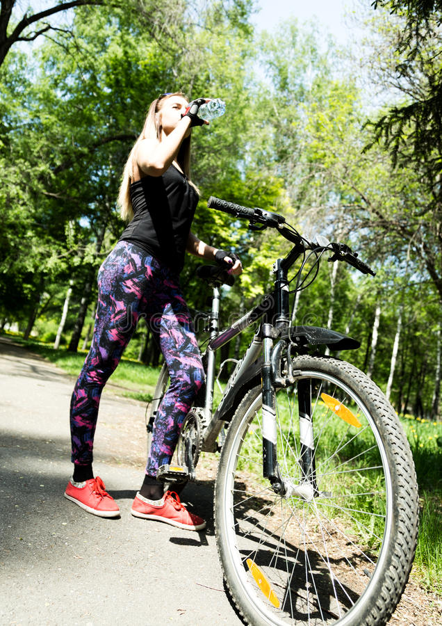 Portret ładna młoda kobieta z bicyklem w parku - plenerowym pije wodę od butelki zdjęcia stock