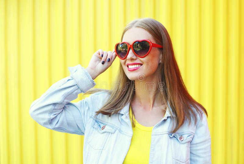 Portret ładna młoda uśmiechnięta kobieta w czerwonych okularach przeciwsłonecznych nad żółtym tłem zdjęcie royalty free