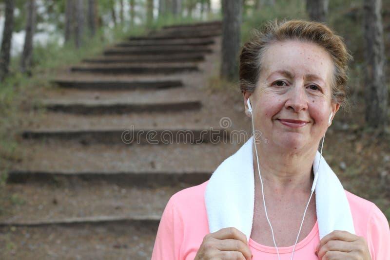 Portret ładna starsza kobieta słucha muzyka po biegać Trenować outdoors w ranku zdjęcie stock