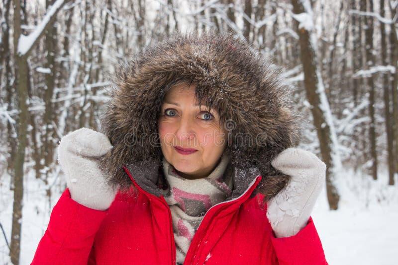 Portret ładna starsza kobieta w zimy śnieżnym drewnie w czerwonym żakiecie obraz stock