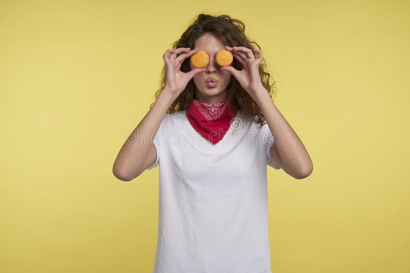 Portret ładnej brunetki włoska kobieta i macarons nad żółtym tłem fotografia royalty free