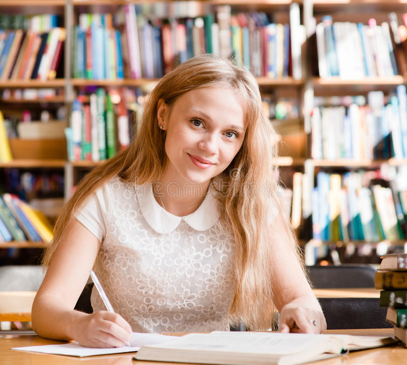 Portret ładny żeńskiego ucznia studiowanie w bibliotece z otwartą książką zdjęcie royalty free