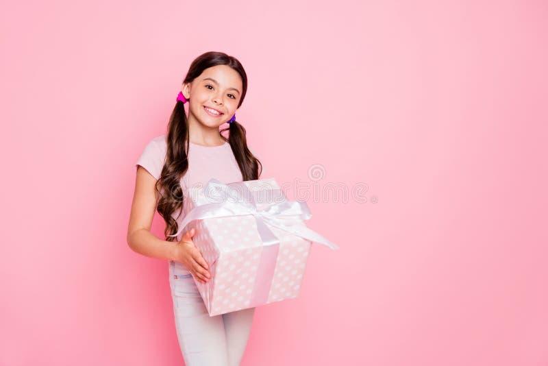 Portret ładny dziewczyny mienia giftbox patrzeje ubierającego biel dyszy spodnia nad różowym tłem zdjęcie royalty free