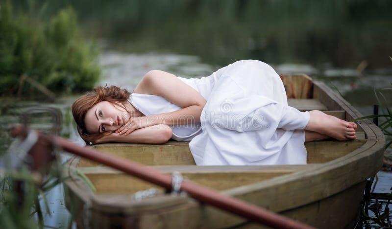 Portret ładny młodej kobiety lying on the beach w łodzi na brzeg rzeki fotografia stock