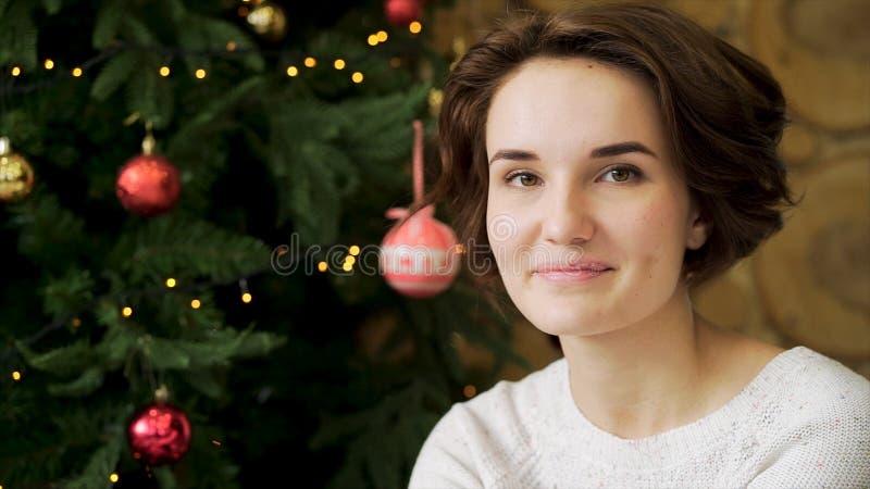Portret ładny, ono uśmiecha się, brunetki dziewczyna świętuje nowego roku przed choinką Potomstwa, piękna kobieta obraz stock
