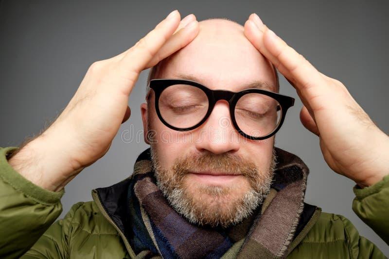 Portret łysy dorosły mężczyzna z brodą toching jego głowę z palcami Jest spokojem i zawartością fotografia stock