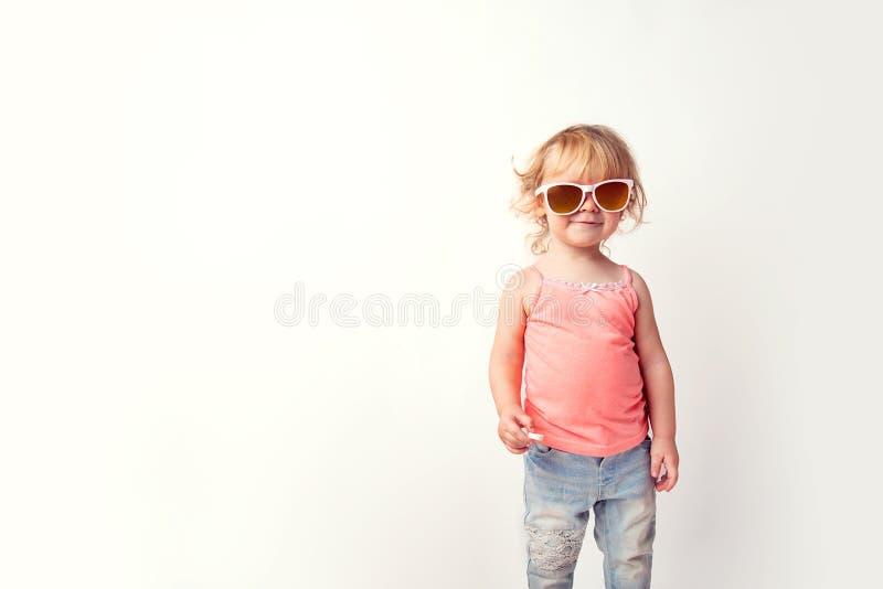 Portret śliczna śmieszna Kaukaska dziecko modnisia dziewczyna w koszulki okularach przeciwsłonecznych z pastylką od ruch choroby  obraz royalty free