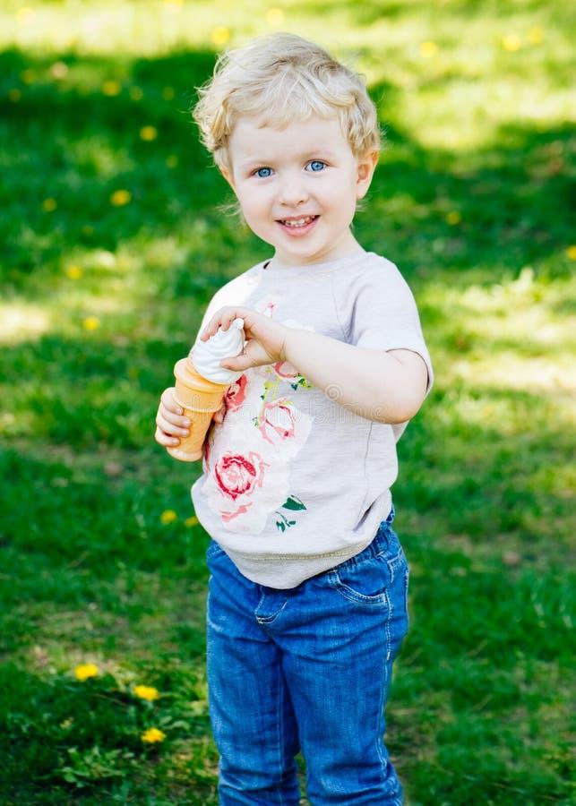 Portret śliczna śmieszna mała blond Kaukaska dziecko dziewczyny berbecia pozycja w zielonego lasu pola łąkowych podmuchowych mydl obraz stock