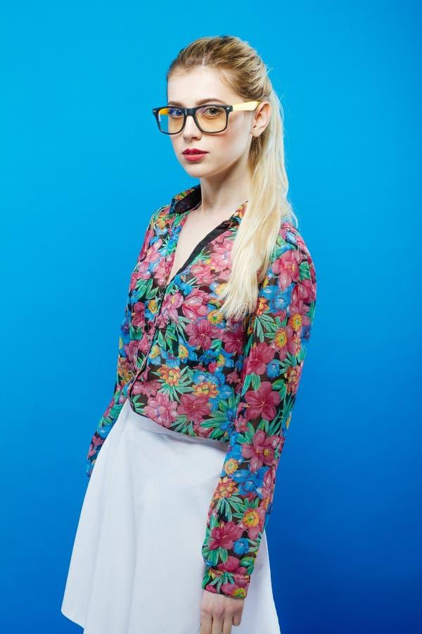 Portret Śliczna blondynki kobieta Jest ubranym Kolorową koszula, biel spódnicę i Eyeglasses na Błękitnym tle z Ponytail, obraz royalty free