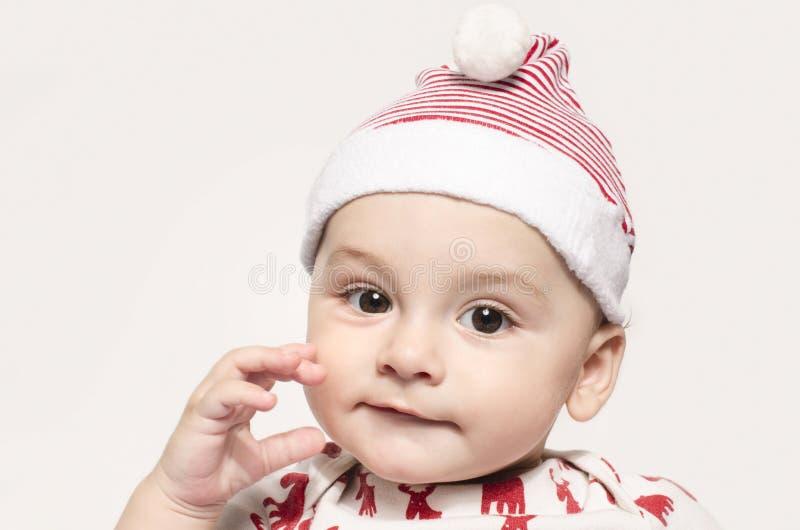 Portret śliczna chłopiec patrzeje kamerę jest ubranym Santa kapelusz zdjęcie stock
