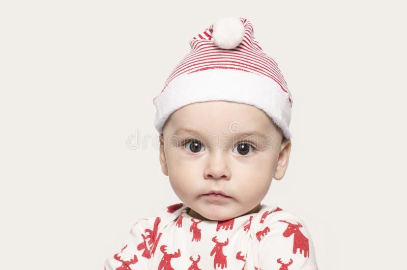 Portret śliczna chłopiec patrzeje kamerę jest ubranym Santa kapelusz fotografia stock