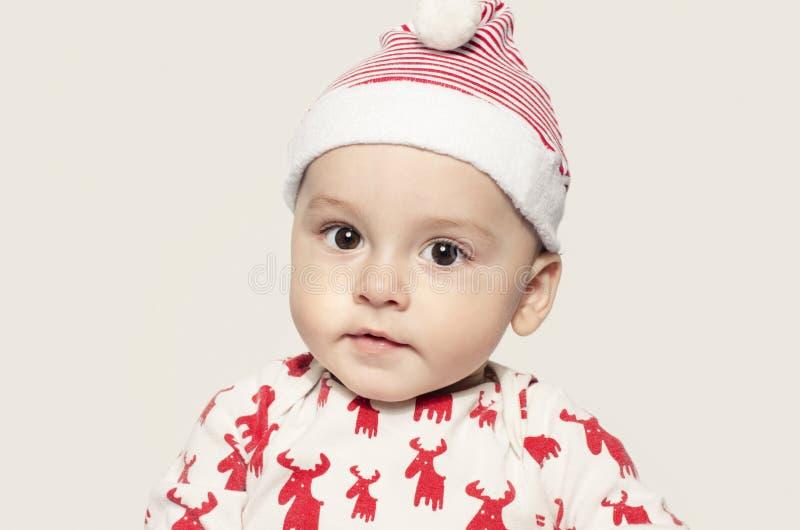 Portret śliczna chłopiec patrzeje kamerę jest ubranym Santa kapelusz obrazy royalty free