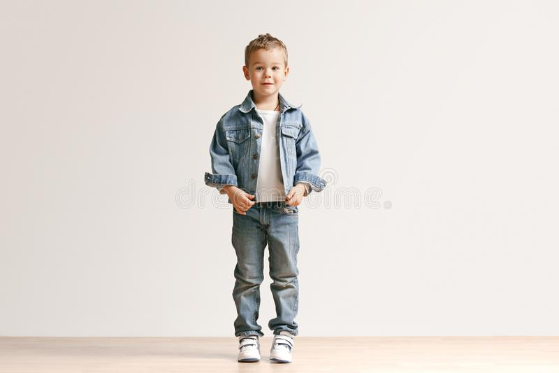 Portret śliczna chłopiec patrzeje kamerę przy studiiem w eleganckich cajgów ubraniach zdjęcia stock