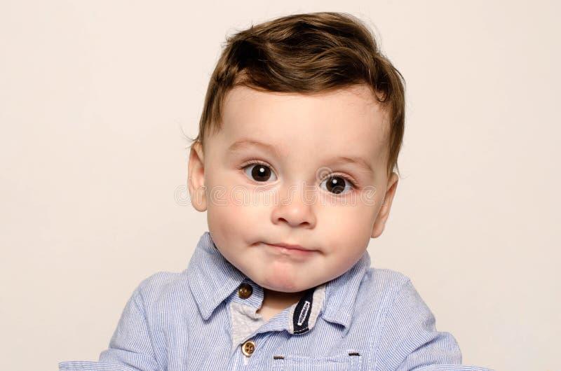 Portret śliczna chłopiec patrzeje kamery czuć zażenowanie zdjęcie royalty free