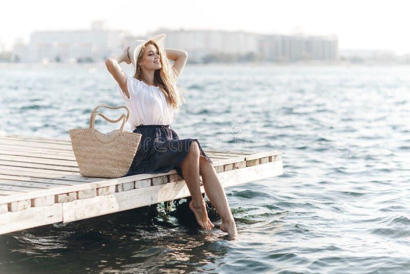 Portret śliczna dziewczyna outdoors w obsiadaniu na molu w wiośnie obraz stock