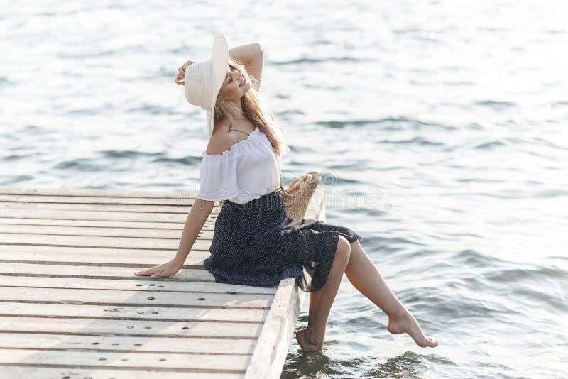 Portret śliczna dziewczyna outdoors w obsiadaniu na molu w wiośnie zdjęcia royalty free