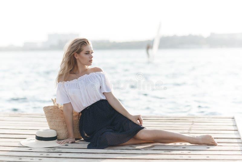 Portret śliczna dziewczyna outdoors w obsiadaniu na molu w wiośnie fotografia stock