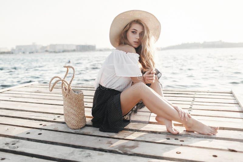 Portret śliczna dziewczyna outdoors w obsiadaniu na molu w wiośnie obraz royalty free