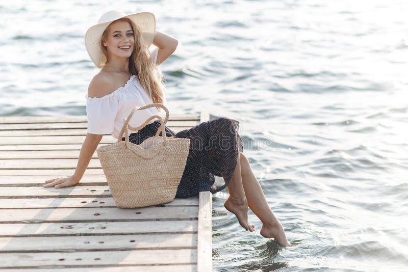Portret śliczna dziewczyna outdoors w obsiadaniu na molu w wiośnie zdjęcie royalty free