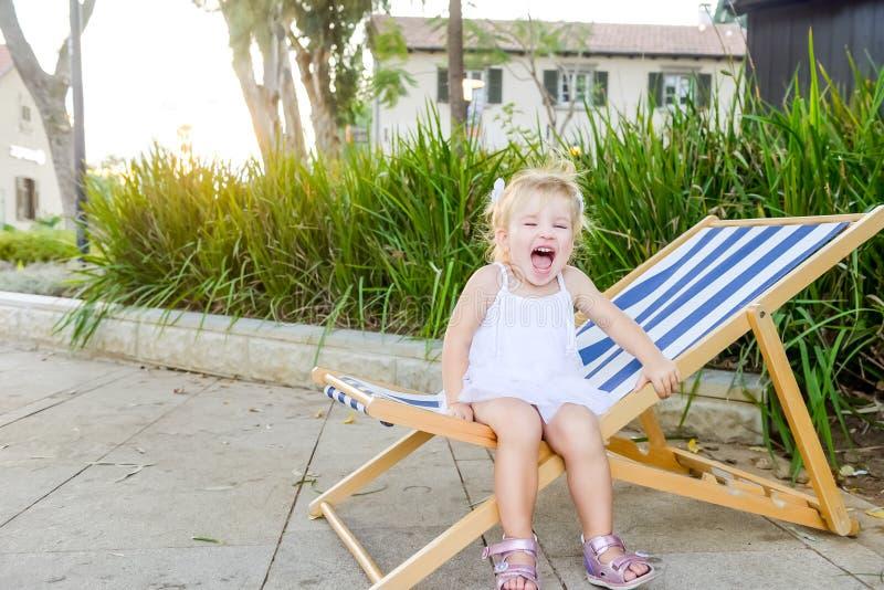 Portret śliczna emocjonalna blondy berbeć dziewczyna w biel sukni obsiadaniu na wrzeszczeć i deckchair Miasto parkowy rekreacyjny zdjęcia stock