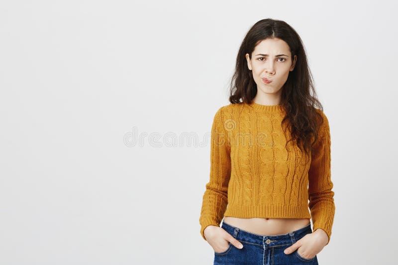 Portret śliczna i modna europejska dziewczyny pozycja z zdumionym wyrażeniem z rękami w kieszeniach, smirking z zdjęcia royalty free