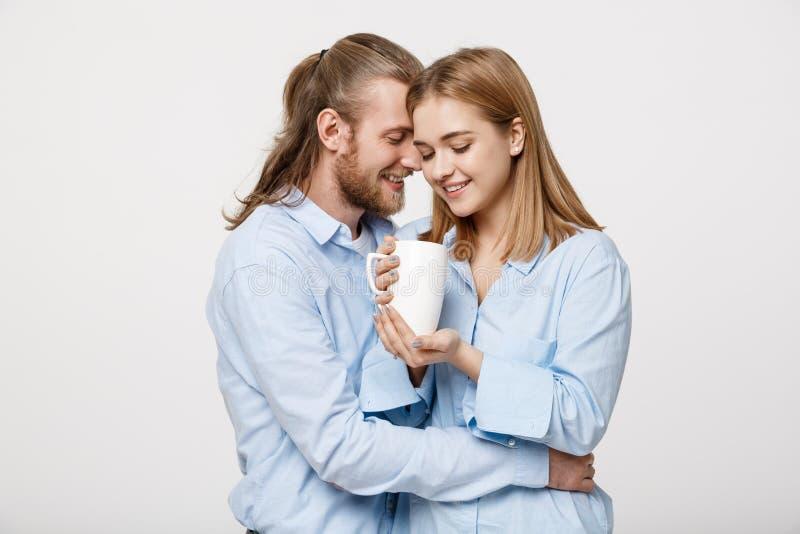 Portret śliczna młoda caucasian para relaksuje wpólnie huging gorącą kawę cieszyć się i fotografia stock