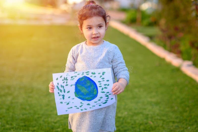 Portret śliczna mała dziewczynka trzyma rysunkową ziemską kulę ziemską Dziecka drawnig obrazek ziemia fotografia royalty free