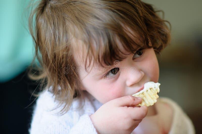 Portret śliczna mała dziewczynka wśrodku łasowanie frytki z kwaśnej śmietanki upadem na nim zdjęcie stock