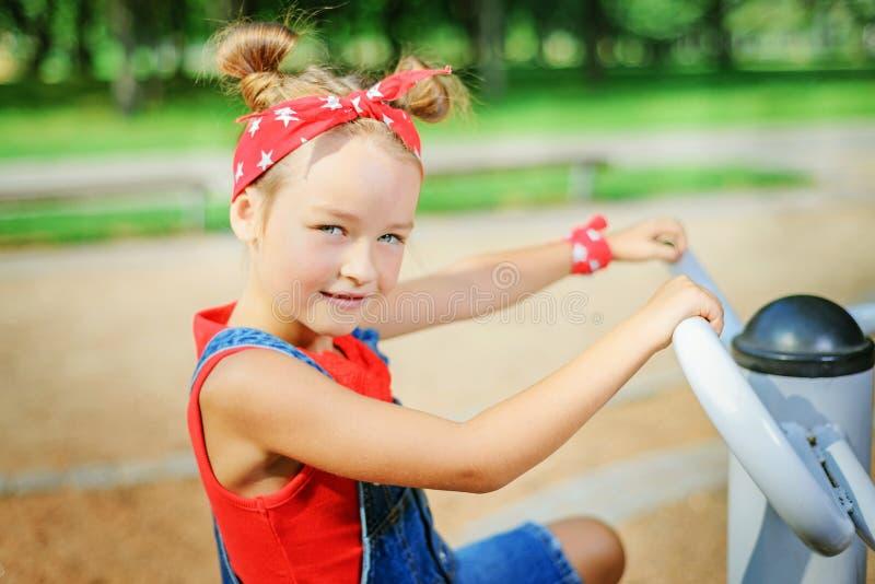 Portret śliczna mała dziewczynka w czerwone bandany Dziecko bawi? si? na boisku obraz stock