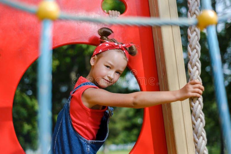 Portret śliczna mała dziewczynka w i chustka na głowę enim kombinezonie i czerwieni koszulce bawić się zabawę i ma zdjęcie royalty free